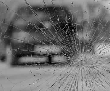 Broken glass from accident being held by window tint